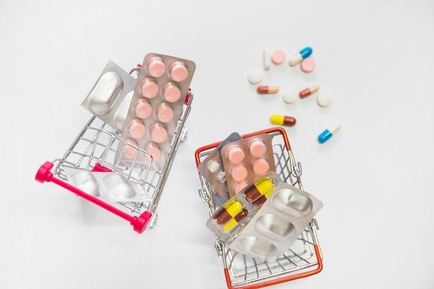 Twee miniatuurboodschappenwagentjes die met pillenblaar worden gevuld op witte achtergrond