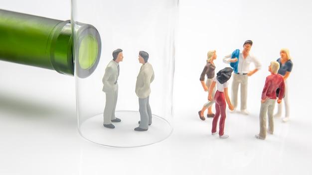 Twee miniatuurpersonen in een glas met een alcoholfles en andere pratende mensen