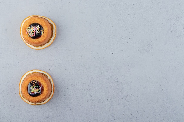 Twee minicakes met gelei die bovenop schijfje sinaasappel worden geplaatst. hoge kwaliteit foto