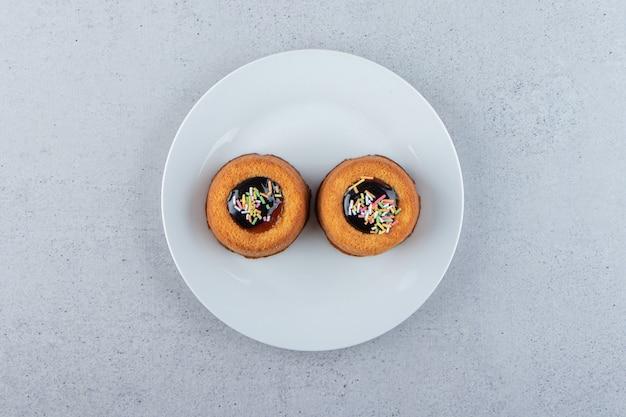 Twee minicakes met gelei die op witte plaat worden geplaatst. hoge kwaliteit foto