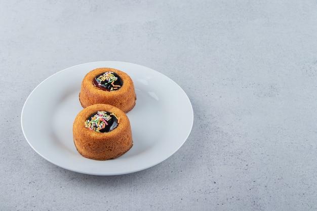 Twee minicakes met gelei op een witte plaat