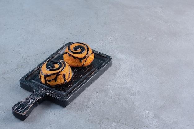 Twee minicakes versierd met chocoladeglazuur op zwart bord.