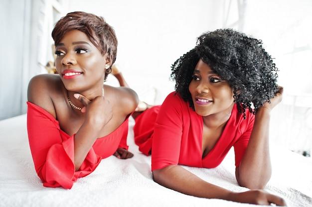 Twee mode afro-amerikaanse modellen in rode schoonheidskleding en gouden hoge hakken, sexy dames poseren avondjurk liggen op het bed.