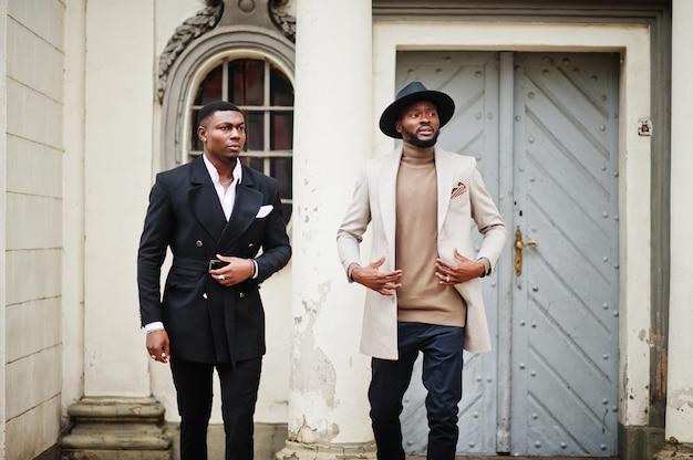 Twee mode zwarte mannen lopen op straat. modieus portret van afro-amerikaanse mannelijke modellen. draag een pak, jas en hoed.