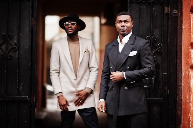 Twee mode zwarte mannen. modieus portret van afro-amerikaanse mannelijke modellen. draag een pak, jas en hoed.
