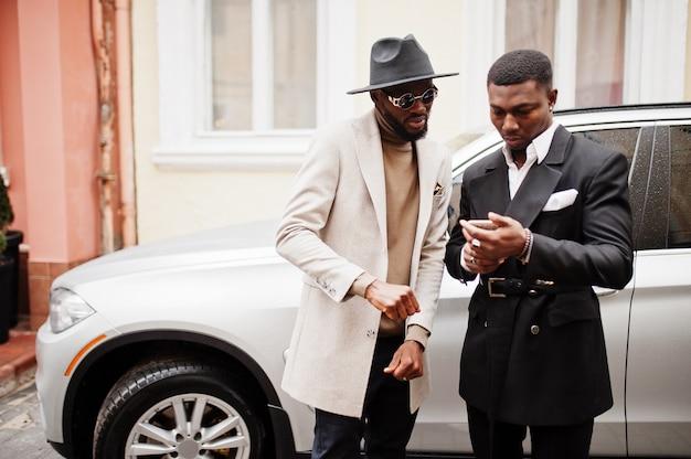 Twee mode zwarte mannen staan in de buurt van zakelijke auto en kijken naar mobiele telefoon. modieus portret van afro-amerikaanse mannelijke modellen. draag een pak, jas en hoed.