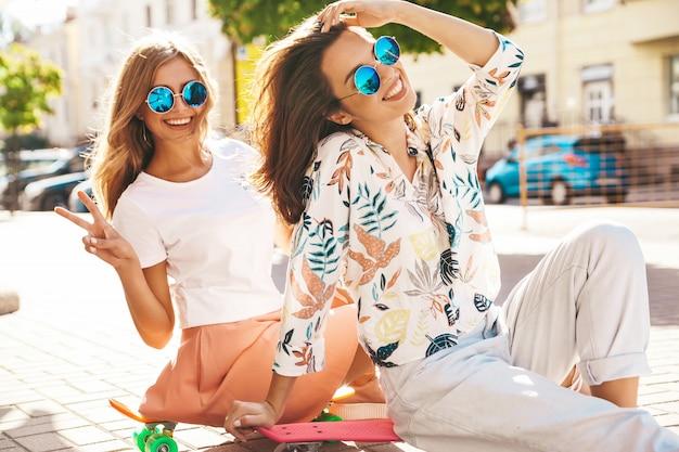 Twee modellen in zonnige zomerdag in hipster kleding zittend op cent skateboard op straat