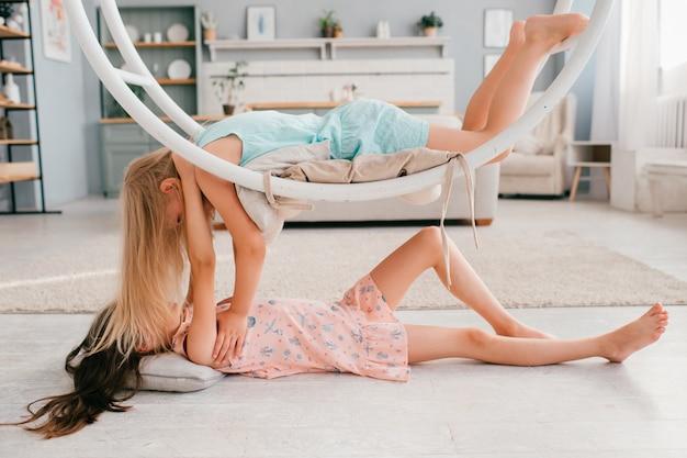 Twee modelmeisjes hebben plezier in de binnenruimte. weinig mooi meisje in roze kleding die onder schommeling met haar vriend ligt die erop ligt.