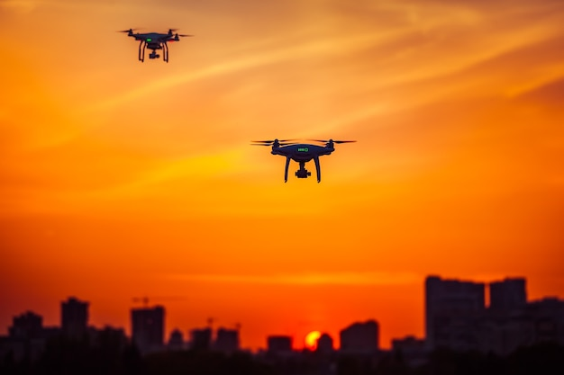 Twee moderne luchtdrones met afstandsbediening vliegen met actiecamera's in het dramatische oranje stadsgezicht van de zonsonderganghemel