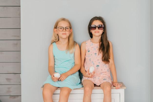 Twee modieuze kleine meisjes in jurken poseren