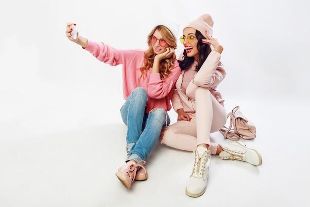 Twee modieuze meiden die zelfportret maken. witte achtergrond. roze kleren.