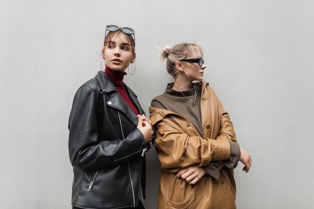 Twee modieuze mooie modelmeisjes in een vintage leren jas met zonnebril in een trui staan in de buurt van een grijze muur in de stad. jeugdstijl