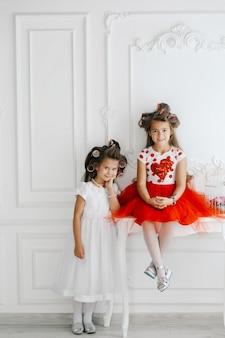 Twee modieuze prinses kleine prinsessen in haar krulspelden kijken naar elkaar en glimlachen