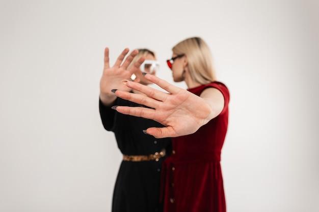 Twee modieuze tienermeisjes in mooie jeugdige kleding in een stijlvolle bril kijken elkaar aan en bedekken de camera met hun handen