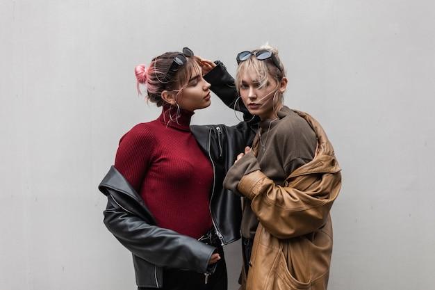 Twee modieuze vriendinnenmeisjes met een leren jas en een gebreide trui staan buiten bij een grijze muur