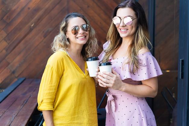 Twee modieuze vrouwen die koffie in koffie drinken