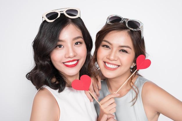 Twee modieuze vrouwen in mooie jurken die samen staan en een rode hartvorm vasthouden.