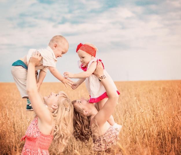 Twee moeders met kinderen in veld