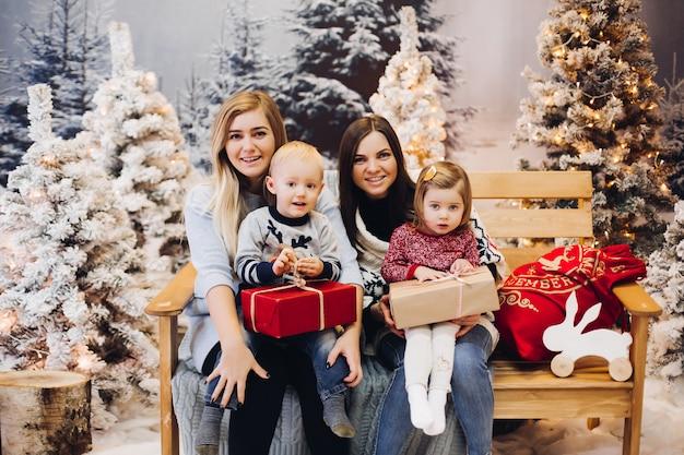 Twee moeders zitten met schattige kinderen en houden kerstcadeautjes