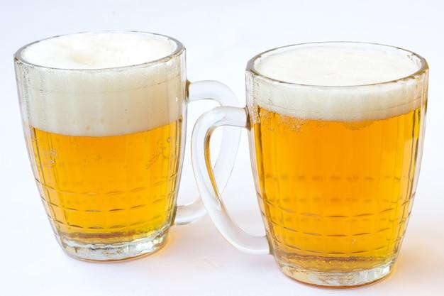 Twee mokken bier op een witte achtergrond