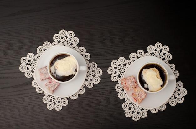 Twee mokken koffie met ijs. bovenaanzicht, zwarte achtergrond