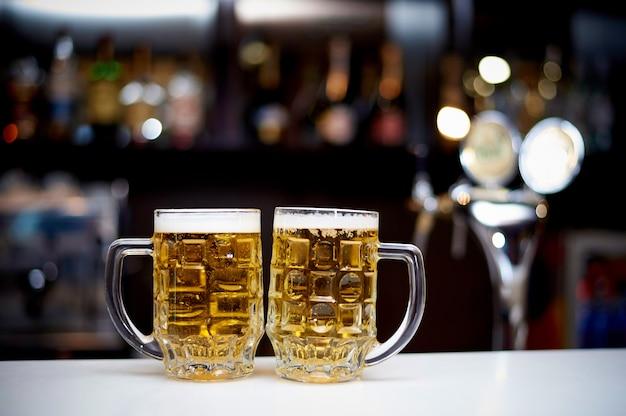 Twee mokken koud bier staan op de bar.
