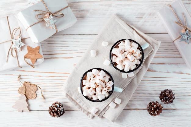 Twee mokken met cacao en marshmallows in kerstversiering op een witte houten tafel. milieuvriendelijke vakantie. bovenaanzicht