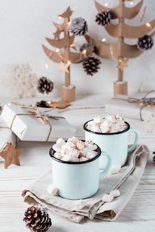 Twee mokken met cacao en marshmallows in kerstversiering op een witte houten tafel. milieuvriendelijke vakantie. verticale weergave