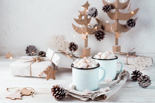 Twee mokken met cacao en marshmallows in kerstversiering op een witte houten tafel. milieuvriendelijke vakantie