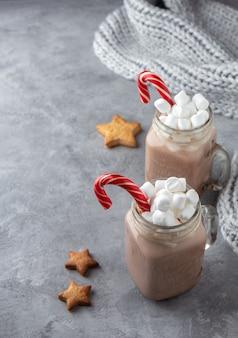 Twee mokken met warme chocolademelk en marshmallows met gemberkoekjes op een grijze achtergrond