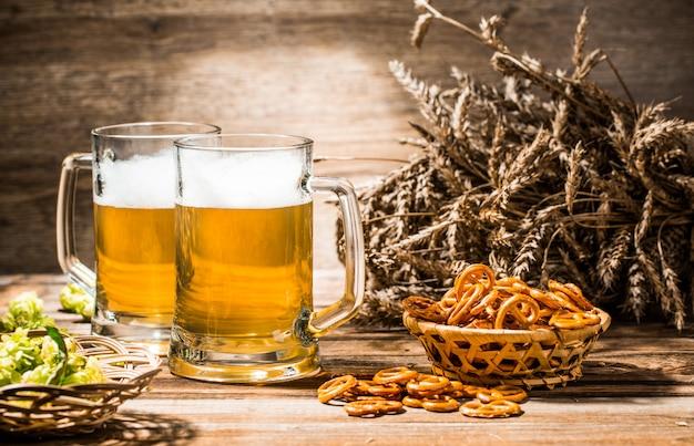 Twee mokken schuimbier met pretzels, tarwe en hop