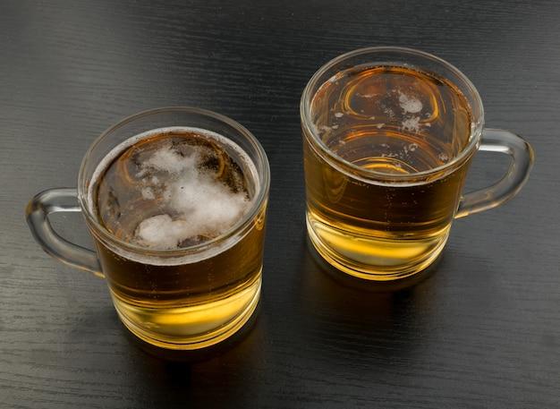Twee mokken van licht bier op zwart