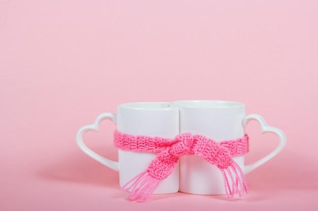 Twee mokken verpakt in sjaal op roze achtergrond