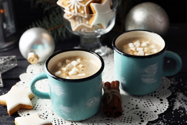 Twee mokken warme cacao met marshmallow en koekjes op zwarte tafel