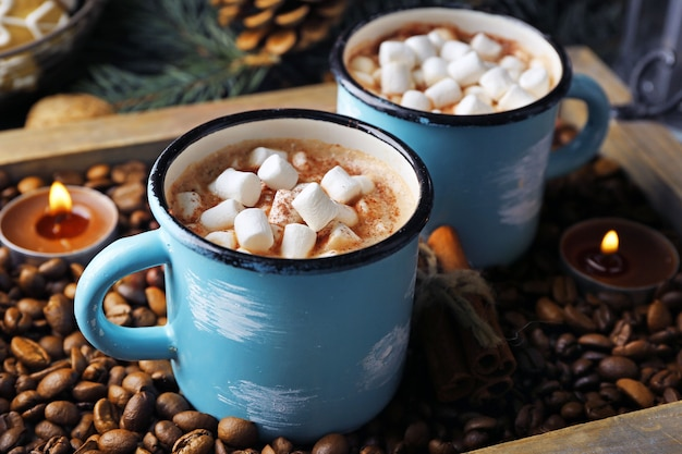 Twee mokken warme cacao met marshmallow op koffiebonen