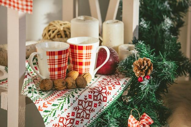 Twee mokken warme chocolademelk in de close-up van het kerstmisdecor