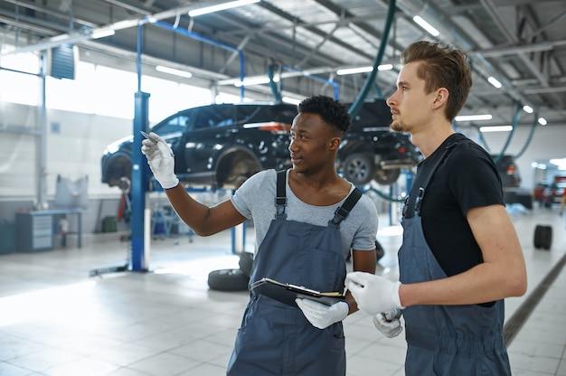 Twee monteur mannen praten in autoservice.