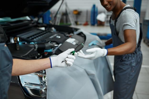 Twee monteur mannen repareert motor in mechanische werkplaats.