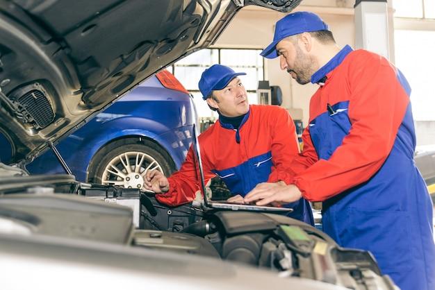 Twee monteurs die werken aan een motor van een auto