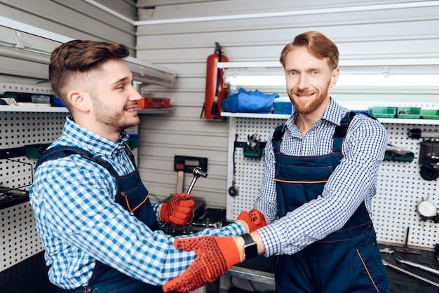 Twee monteurs schudden elkaar de hand en glimlachen.