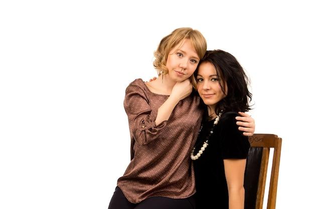 Twee mooie aanhankelijke jonge vriendinnen poseren op een stoel met hun armen om elkaar heen op wit