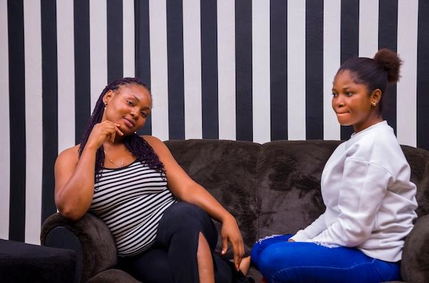 Twee mooie afrikaanse dames poseren terwijl ze op een bank zaten