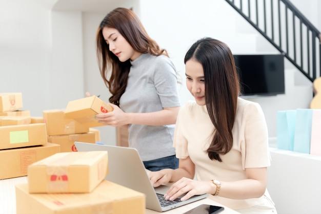 Twee mooie aziatische vrouwen controleren bestellingen via laptops via internet
