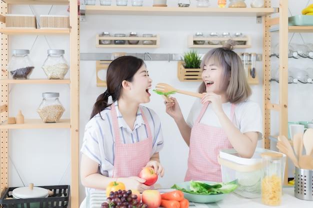 Twee mooie aziatische vrouwen, thaise mensen dragen vrijetijdskleding en dragen roze schorten, helpen elkaar koken en hebben plezier bij het proeven van eten in de keuken