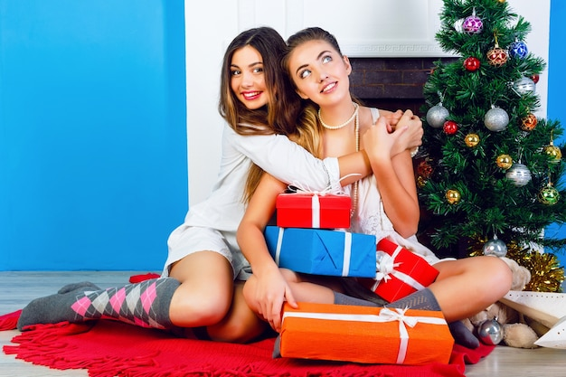 Twee mooie beste vrienden meisjes openen kerstcadeautjes in de buurt van open haard en versierde nieuwjaarsboom.