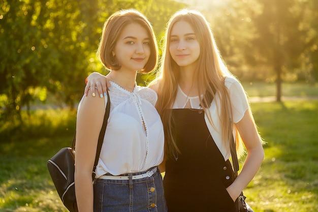 Twee mooie beste vriendinnen schoolmeisjes (student) ontmoeten elkaar in het park