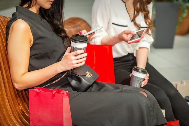 Twee mooie blanke jonge vrouwen kijken in slimme telefoon met tassen zittend op de bank tijdens het rusten in het winkelcentrum