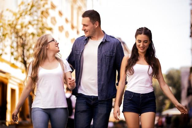 Twee mooie blanke meisjes en een jongen lopen door de straat