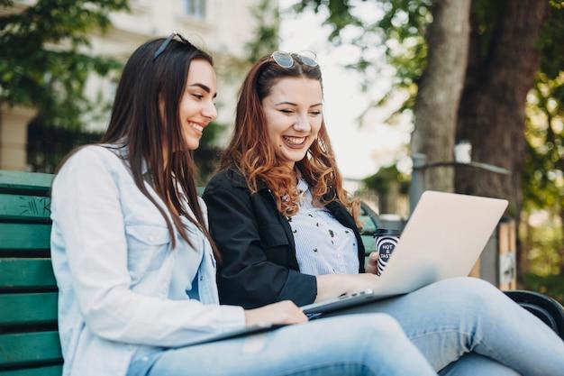 Twee mooie blanke vrouw zittend op een bankje buiten lachen terwijl het kijken naar een laptop op de benen.