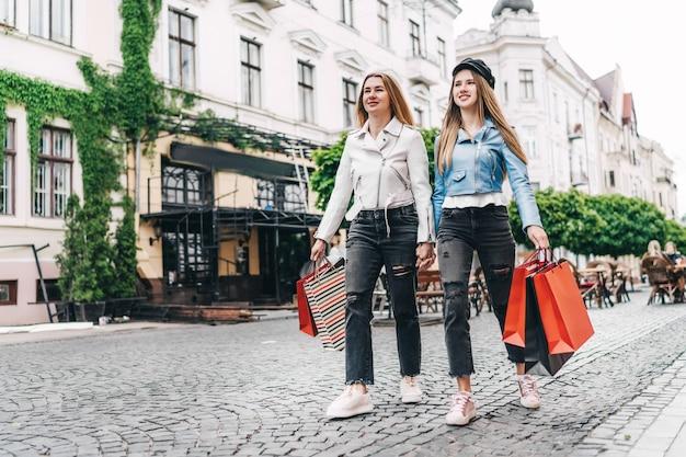 Twee mooie blonde vrouwen, moeder en dochter, lopen door de straten van de stad